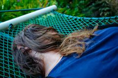 Woman laying down on a hammock and her face covered by her hairs - stock photo