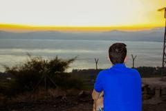 Back view of man watching the sunset at the Sea of Galilee Stock Photos