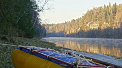 Raft on shore of mountain misty river - stock footage