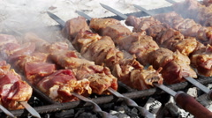 Cooking of pork shashlik on skewers on the grill - stock footage