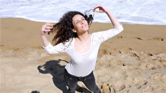 Slow motion of  young woman enjoying the summer sun on sea shore, low angle shot Stock Footage