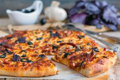 Appetizing pizza with salami, black olives and cheese close up. - stock photo