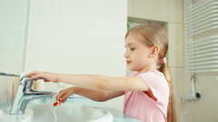 Girl child 7-8 years old cleaning teeth in bathroom and smiling at camera Stock Footage