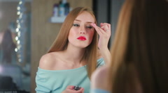 Girl puts make-up before a mirror. He is going on a date Stock Footage