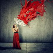 Beautiful woman in red dress using an umbrella as shelter against red drops p Stock Photos