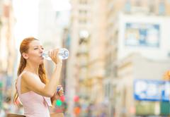 Thirsty young woman. Woman drinking water from plastic bottle in a city on a  Stock Photos