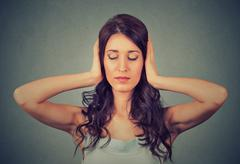 Relaxed woman with eyes closed covering her ears with hands - stock photo