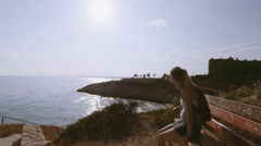 Pretty happy woman in sunglasses relaxing on bench by the sea - stock footage