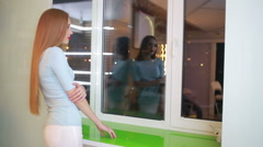 Women standing by the windowsill, looking out of window. night city Stock Footage