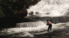 Young man fly fishing by large waterfall Stock Footage