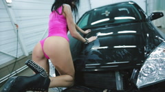 Sexy young girl in a pink dress posing on the car - stock footage