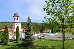 Bell tower and basin at orthodox Curchi monastery in Moldova with green trees Stock Photos