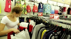Woman in a supermarket. The girl in the shop.Buy sportswear. Clothing store - stock footage