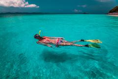 The young lady with snorkel and fins Stock Photos