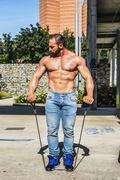 Muscular Shirtless Hunk Man Exercising with Elastic Bands - stock photo