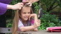 Girl bored until my mother braids her long hair and looking at the reflection Stock Footage