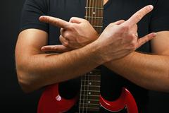Hands with red guitar and devil horns on black - stock photo