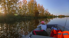 Rubber boat with fisher moving near riverside with yellow trees Stock Footage