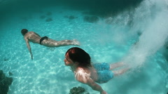 Two men jumping into the blue ocean. Underwater shooting Stock Footage