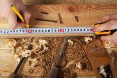 Carpenter working, hammer, meter and screw-driver on construction background Kuvituskuvat