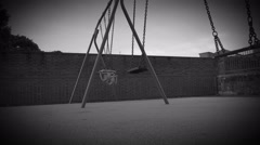 black and white creepy childs empty playground toy swings - stock footage