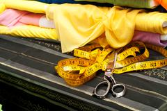 Sewing textile or cloth. Work table of a tailor. Scissors, measuring tapes. Top - stock photo