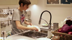 Teenager Boy Washing Dishes in the Sink Stock Footage