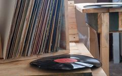 Vinyl record with copy space in front of a collection albums dummy titles - stock photo