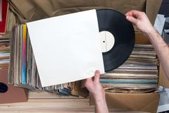 Browsing through vinyl records collection. Music background. Copy space. Retro - stock photo