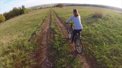 Young lady cycling on a countryside road at summer sunny day Stock Footage