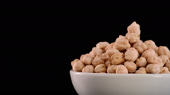 Chickpeas vegetables gyrating on black background justified at right - stock footage