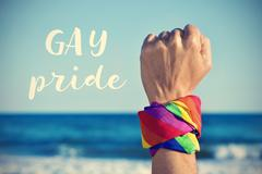 Text gay pride and a raised fist with a rainbow-patterned kerchief Stock Photos
