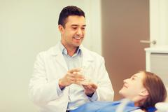 happy dentist showing jaw layout to patient girl - stock photo