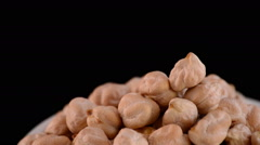 Chickpeas vegetables gyrating on a bowl on black background - stock footage
