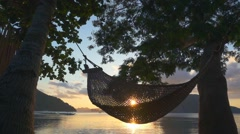 Hammock at sunset on the beach. Slow motion Stock Footage