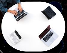 Top View of Rounded Desk with Four Laptops Stock Photos