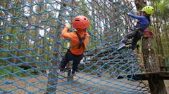 Boy climbing in adventure park Stock Footage