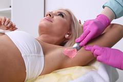 Waxing armpit hair - stock photo