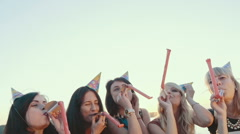 A friendly group of girls celebrating on the beach. Holiday horns and hats Stock Footage