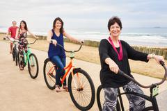Happy healthy family smiling at the camera on bicycles - stock photo