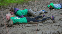 Girls are crawling in the mud pool Stock Footage