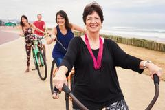 Happy family and pround mother smiling on bicycles - stock photo