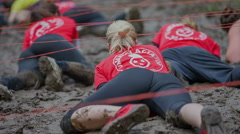 Teams of different colours are crawling in the mud pool Stock Footage