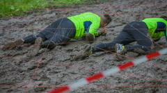 Two guys are crawling across the mud pool very fast Stock Footage