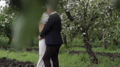 Bride and groom a romantic walk in the apple orchard Stock Footage