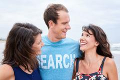 three siblings laughing and smiling at each other - stock photo