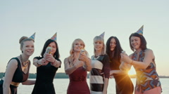 Group of happy friends celebrating the girls at the lake. Firecrackers shoot to Stock Footage