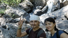 Happy people near waterfall Stock Footage
