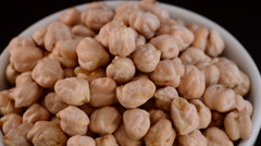 Chickpeas vegetables gyrating on black background, close up - stock footage