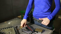 Young woman with the gun. indoor shooting range. charges cartridges in the gun Stock Footage